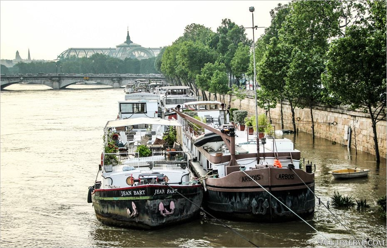 Crue de la Seine - Des péniches et, à peine visible, une voiture qui flotte sur les quais. Le Grand Palais à l'arrière-plan