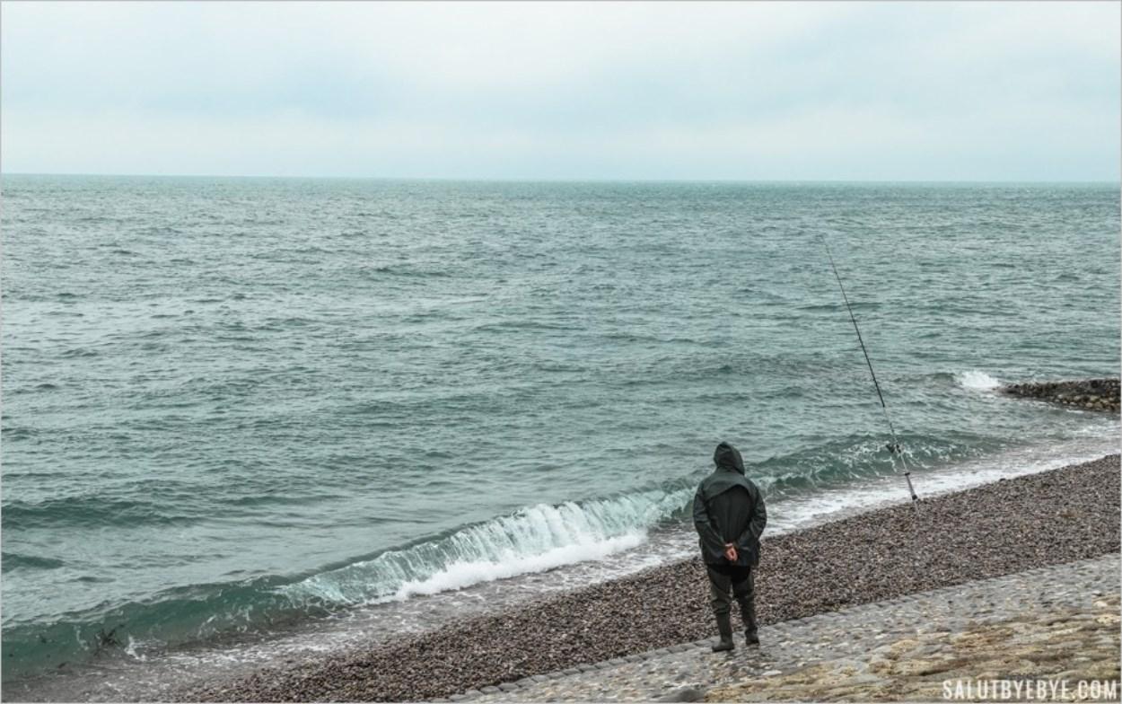 Un pêcheur bravant le mauvais temps sur la plage d'Etretat